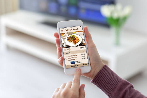 female hands holding phone with app delivery food on screen - food delivery стоковые фото и изображения