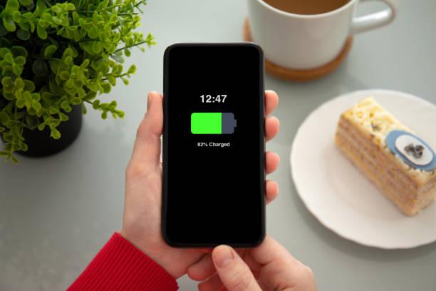 weibliche hände halten telefon mit aufgeladener batterie auf dem bildschirm - sinnvolle wörter stock-fotos und bilder
