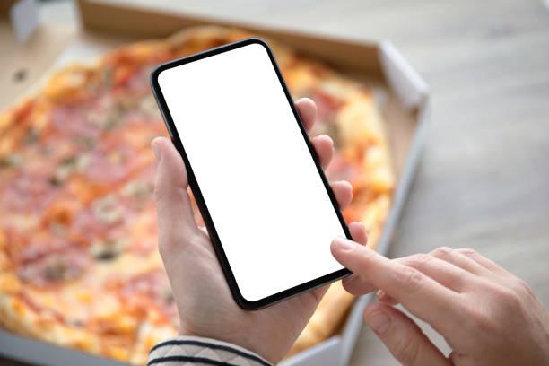 weibliche Hände halten Telefon mit isoliertem Bildschirm über Pizza-Box – Foto