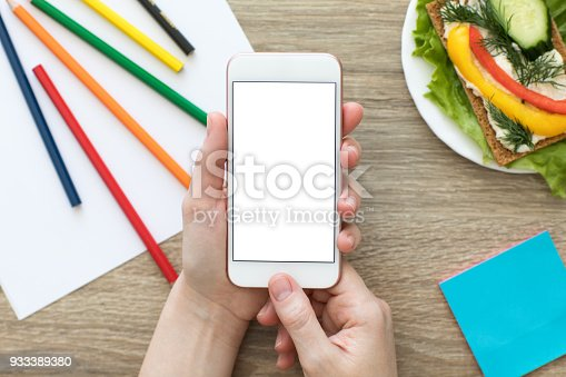 936543982 istock photo Female hands holding phone with isolated screen in  colorful cafe 933389380