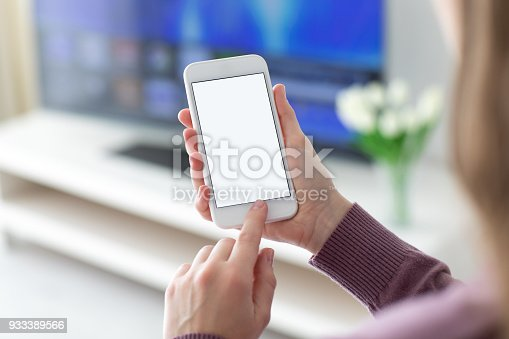 936543982 istock photo Female hands holding phone with isolated screen in room 933389566