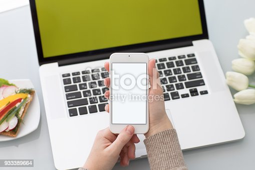 936543982istockphoto Female hands holding phone with isolated screen on laptop background 933389664