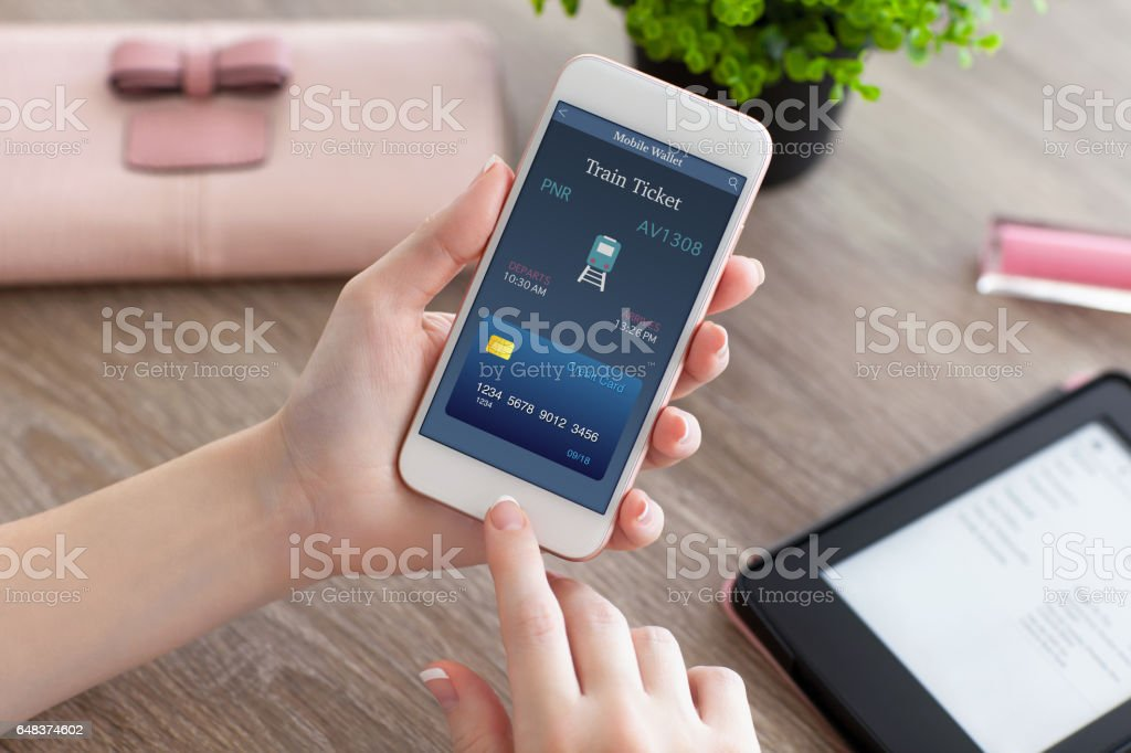 female hands holding phone with online train ticket on table stock photo