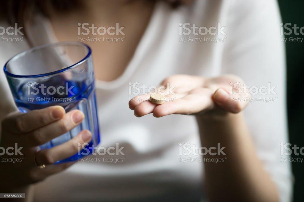 Weibliche Hände halten, Pille und ein Glas Wasser, Nahaufnahme – Foto