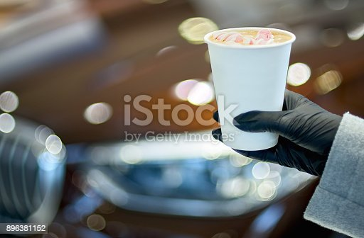 women's hands with a paper cup of coffee with marshmallows - close up.