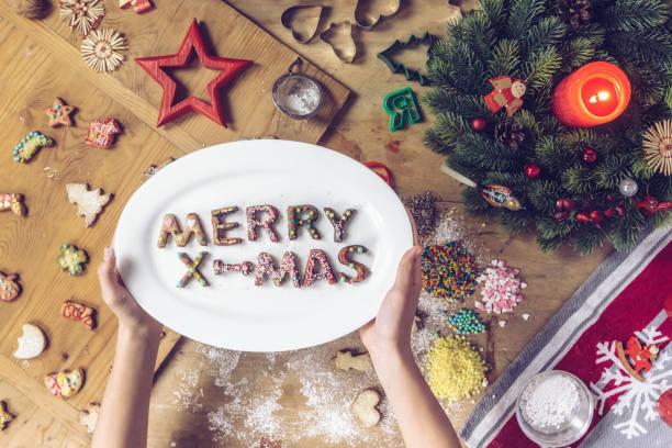 weibliche hände halteplatte mit frohe weihnachten briefe von cookies gemacht - handbemalte teller stock-fotos und bilder
