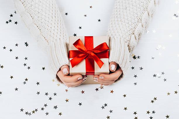 female hands holding present with red bow - damen top gold stock-fotos und bilder