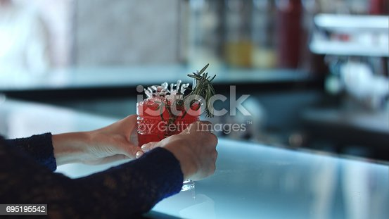 istock female hands holding red cocktail in the bar 695195542