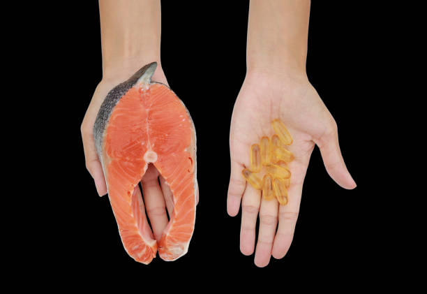 Female hands holding Red fish salmon fillet with Fish oil capsules on black background. stock photo