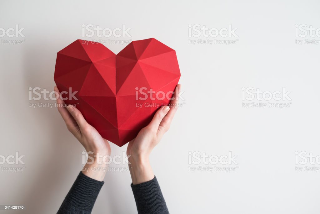 Female hands holding red polygonal heart shape - foto stock