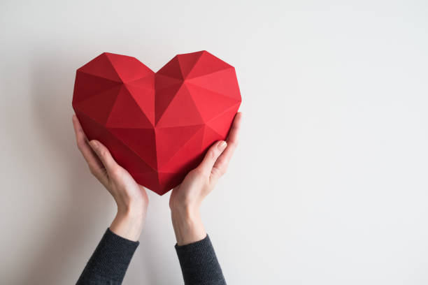 female hands holding red polygonal heart shape - accudire foto e immagini stock