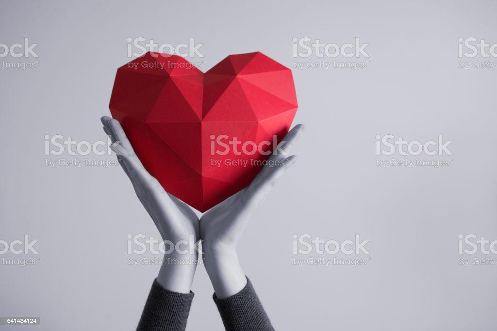 Female hands holding red polygonal heart shape – Foto