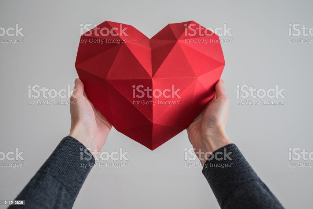 Weibliche Hände halten rote polygonalen Herzform – Foto