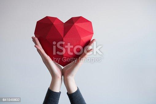 istock Female hands holding red polygonal heart shape 641545802
