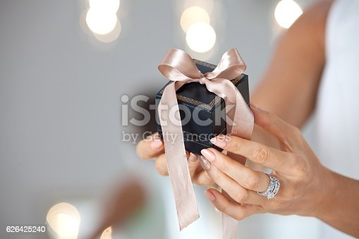 istock Female hands holding small elegant gift with ribbon. 626425240