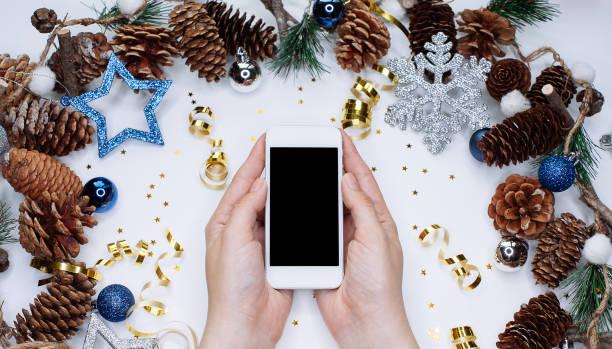 Weibliche Hände halten smart Handys auf weißem Hintergrund mit Weihnachten Kegel, Schneeflocken und Konfetti – Foto