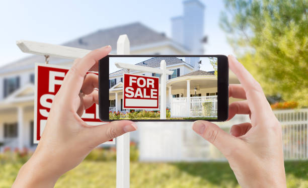 Female Hands Holding Smart Phone Displaying Photo of For Sale Real Estate Sign and House Behind. stock photo
