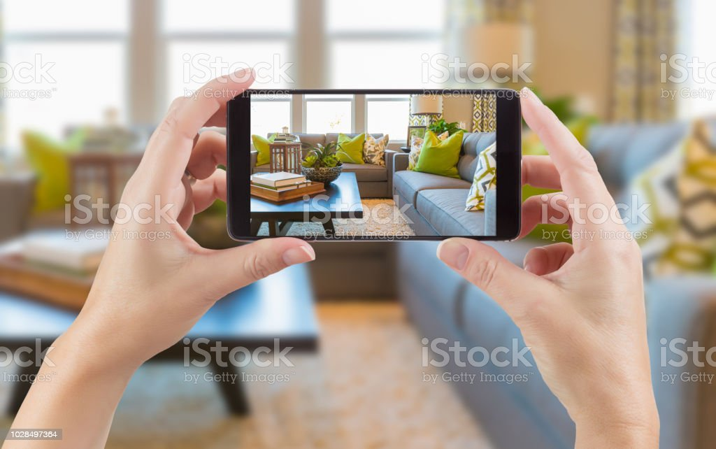 Female Hands Holding Smart Phone Displaying Photo of House Interior Living Room Behind. stock photo