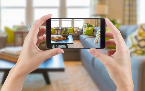 手持智慧手機的女性手在背後展示房子內部起居室的照片。 - 摄影 個照片及圖片檔