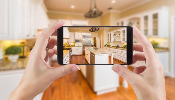 vrouwelijke handen met slimme telefoon weergeven foto van keuken achter. - tonen stockfoto's en -beelden