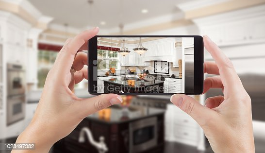 Female Hands Holding Smart Phone Displaying Photo of Kitchen Behind.