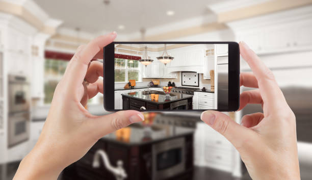 Female Hands Holding Smart Phone Displaying Photo of Kitchen Behind. stock photo