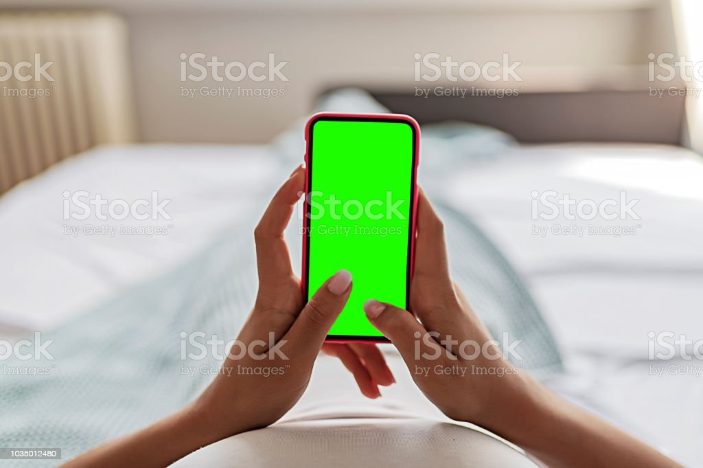 Female Hands Holding Smart Phone With Chroma Key Green Screen stock photo