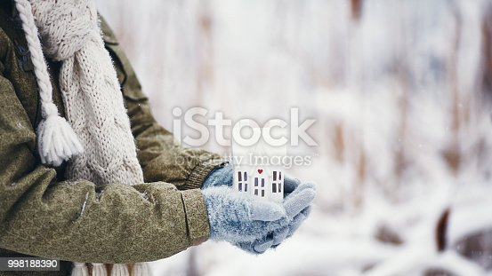 Female hands holding tiny house in snowy weather