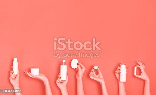 istock Female hands holding white cosmetics bottles - lotion, cream, serum on trendy coral color background. Square crop. Skin care, pure beauty, body treatment concept. Banner with copy space 1160060322