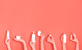 Female hands holding white cosmetics bottles - lotion, cream, serum on trendy coral color background. Square crop. Skin care, pure beauty, body treatment concept. Banner with copy space.