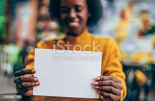 Young beautiful african-american woman holding in hands white empty blank paper page with copy space.