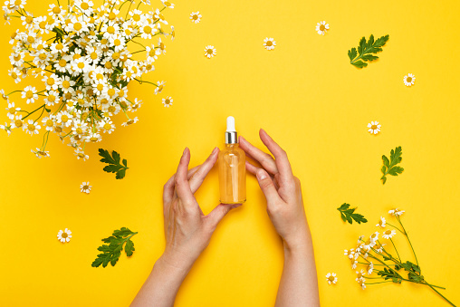 1151624350 istock photo Female hands holds a dropper glass bottle of essence or serum 1271308742