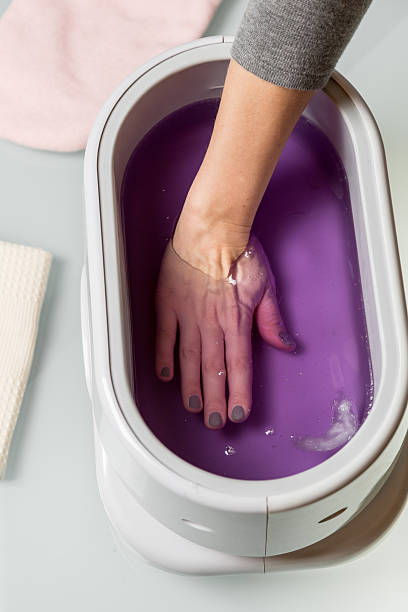 Female Hands In A Paraffin Wax Bowl Stock Photo