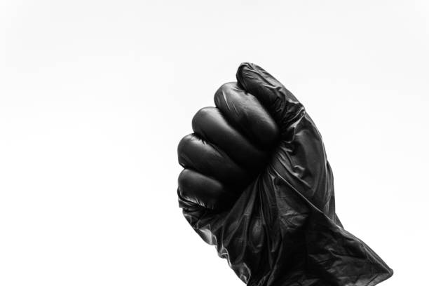 Female hands in black gloves show gestures, signs and symbols isolated on white background. All fingers clenched into a fist. Aggression or hit, game stone. stock photo