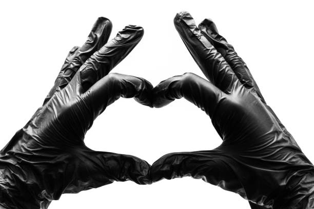 Female hands in black gloves show gestures, signs and symbols isolated on white background. Two hands fingers folded in the form of a heart and love stock photo