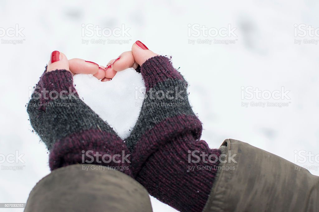 Female hands in gloves holding a snow shaped heart stock photo