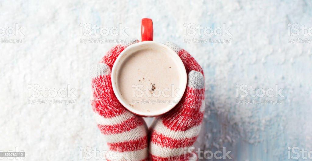 mãos femininas em luvas segurando chocolate quente - foto de acervo