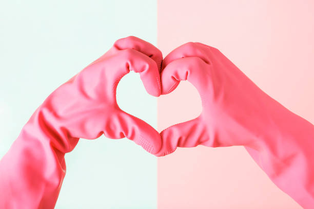 Female hands in gloves in the shape of a heart on blue and pink background, cleaning concept stock photo