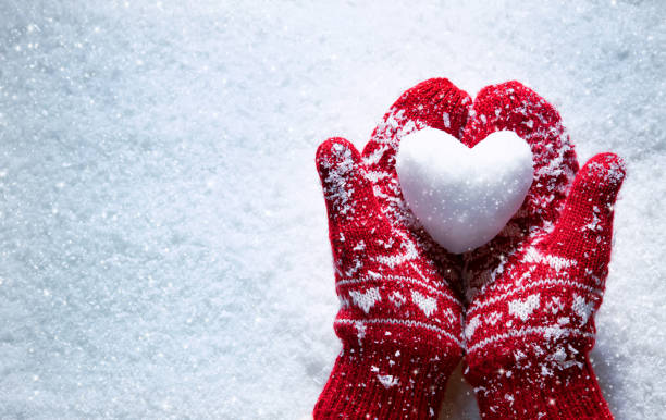 Female hands in knitted mittens with snowy heart against snow background stock photo