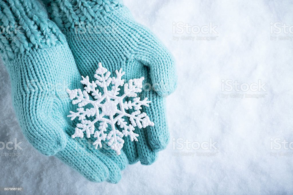 Female hands in light teal knitted mittens with sparkling wonder stock photo