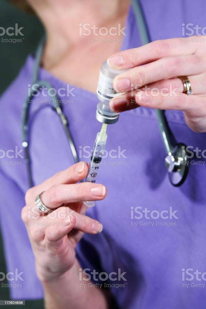 Female hands in purple scrubs inserting needle into bottle royalty-free stock photo