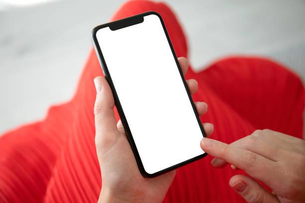 weibliche Hände in rotem Kleid halten Telefon mit einem isolierten Bildschirm – Foto