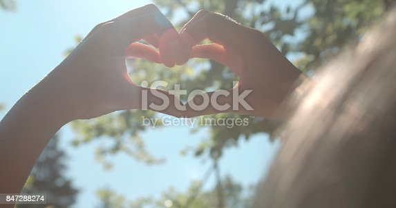 Young woman rising hands and showing heart.