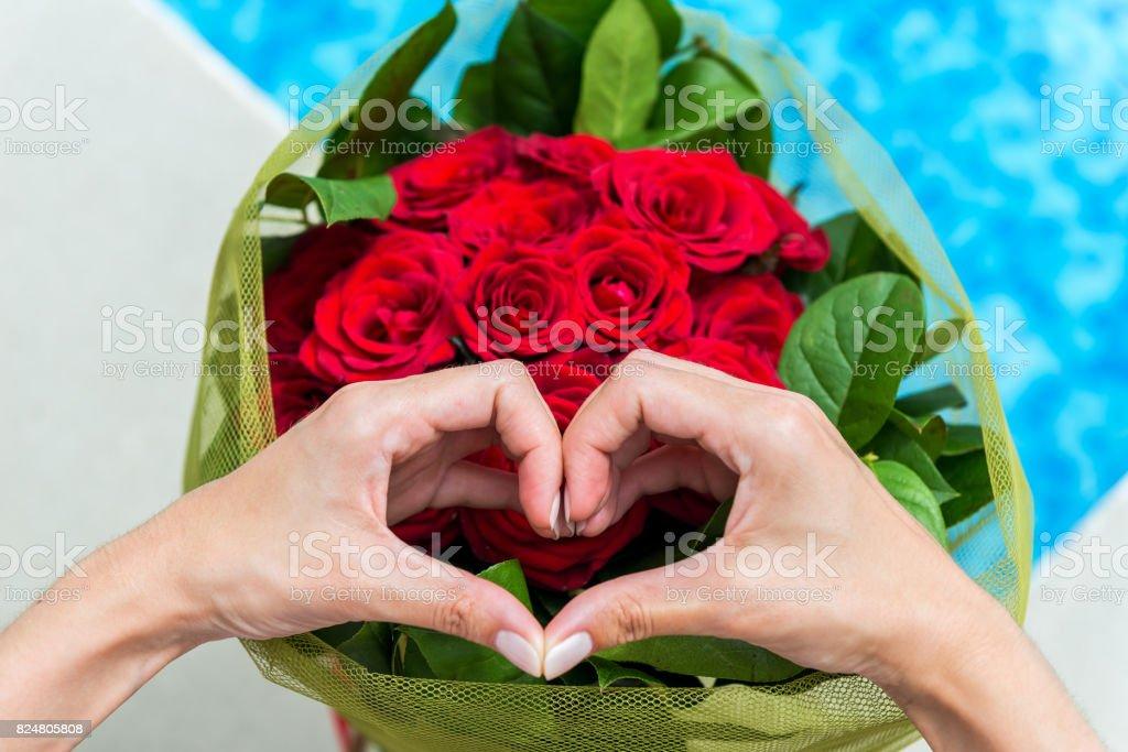 Mãos femininas em forma de coração e buquê - foto de acervo