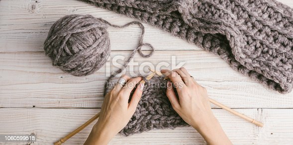 Knitting. Gray stylish thick thread and tangle. Female hands in the process of knitting. Calm stylish hobby