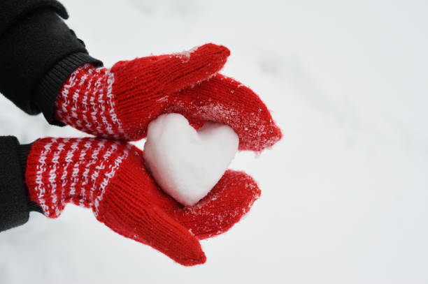 female hands in warm red crocheted mittens with snowy heart. white snow background. love concept. valentine's day greeting card with copyspace - mitene imagens e fotografias de stock