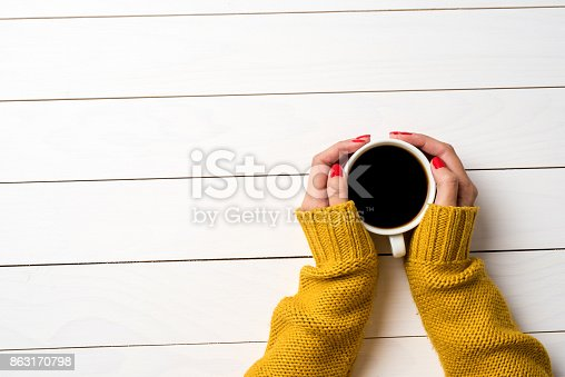 istock Female hands in warm sweater holding cup of coffee 863170798