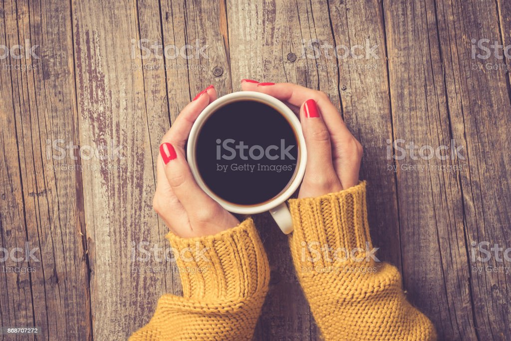 Female hands in warm sweater holding cup of coffee royalty-free stock photo