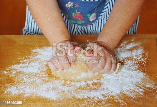 istock female hands kneading a dough 1186490355