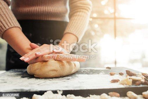 istock Female hands kneading dough, sunset background 619508966